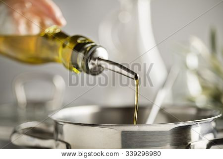 Cooking Meal In A Pot. Bottle Of Extra Virgin Oil Pouring In To Pot For Cooking Meal. Healthy Food C