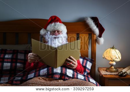 Santa Claus sitting in bed reading a large book before he goes to sleep on Christmas Eve.