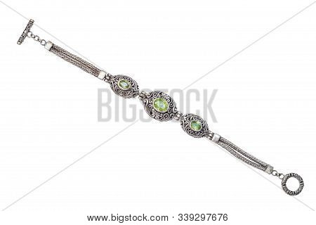 top view of traditional vintage indian silver bracelet with natural green peridot gemstones isolated on white background poster