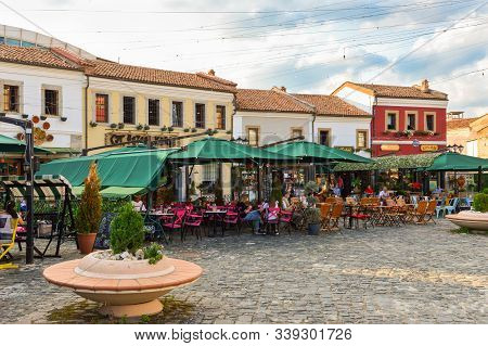 Korce, Albania - July 14, 2019: Old Bazaar Of Korca City With People Hanging Out At Cafes During Sum