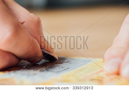 Selective Focus Of Silver Coin In Hand Of Gambler Scratching Lottery Ticket