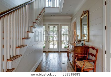 Luxury home entry foyer with view out onto waterfront property.