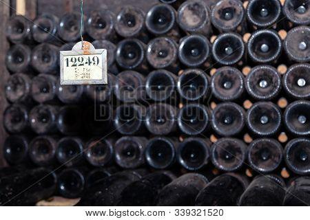 Closeup Pattern From Bottom Of Old Dark Dusty Wine Bottles In Rows In Cellar, Basement, Wine Warehou