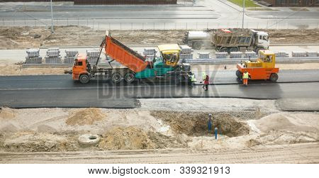 Dump truck unloads asphalt into paver
