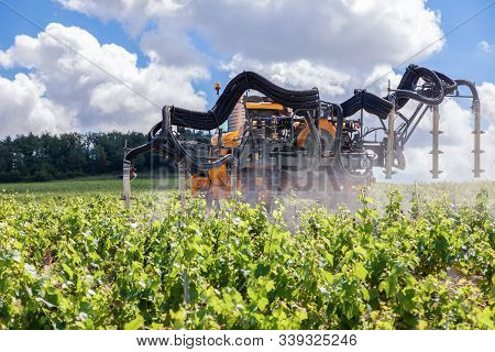 France Chablis 2019-06-21 Orange Tractor Cultivate Field, Tractor Spraying Vineyard With Fungicide,