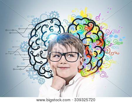 Adorable Smiling Little Boy With Glasses Standing Near Gray Wall With Colorful Left And Right Brain