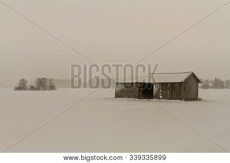 The Snow Storm Covers The Old Wooden Barn House With Frost At The Rural Finland.