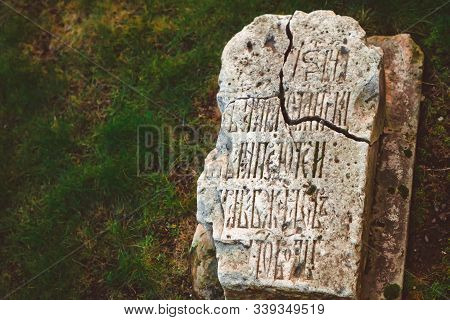 An Ancient Tombstone Of Stone Cracked On The Ground