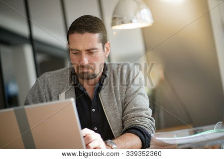 Businessman working late on laptop computer in office