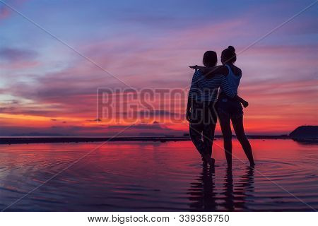 Two Girlfriends Hugging Up And Enjoying A Rose/pink Sunset Sky On The Sea Beach On The Samui Island,