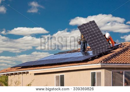 Workers Installing Solar Panels on House Roof.