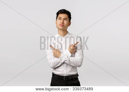 Indecisive And Perplexed Asian Male Entrepreneur Facing Hard Choice, Standing Unsure, Looking Up Tho