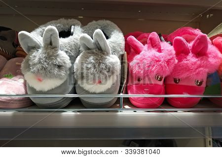 Soft Slippers Bunnies Gray And Pink. Indoor Slippers On Store Shelves. Soft Colored Slippers For Chi