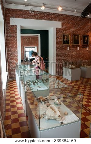 Russia, Vladivostok, July 2018: Seaside Museum V.k. Arsenyev. Tourist Girl Examines Exhibits Of Muse