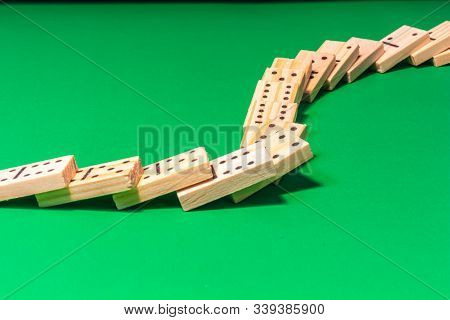 A Curved Line Of Dominoes In A Domino Show Has Been Toppled, With The Wooden Game Pieces Cascading A