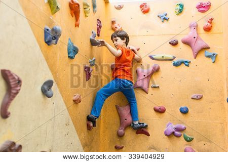 Boy Climbing On Artificial Boulders Wall In Gym
