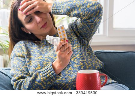 Sick woman with pills on couch. Woman with flu holding pills on couch at home. Sickness. Sick woman at home. At home with flu. Concept of sick woman. Sick people at home.