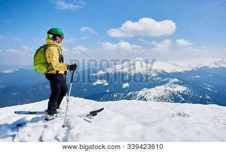Sportsman Skier In Helmet And Goggles With Backpack Standing In Profile On Skis Holding Ski Poles In