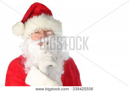 Santa Claus Christmas. Santa holds his finger to his lips and says SHHHHHHHHH. Santa knows if you have been bad or good this year. Isolated on white. Room for text. Santa says Happy Holidays to all.