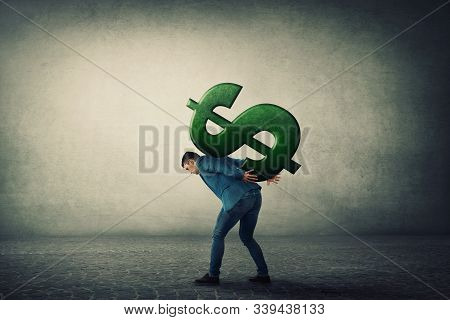 Businessman Carrying A Big American Dollar Sign On His Back. Overloaded Guy, Difficult Burden And De