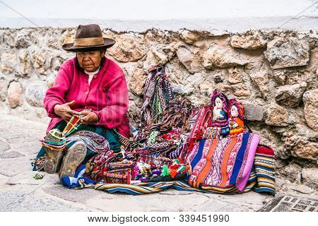 Cusco , Peru- Jan 9, 2019: Old Quechua woman traditional clothing sale colorful tablecloths and fabric at street of  Cusco City, Peru.