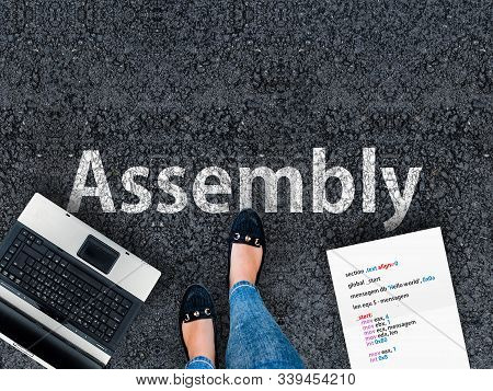 Assembly Programming Language. A Woman Steps To A Laptop And Word Assembly On Asphalt.