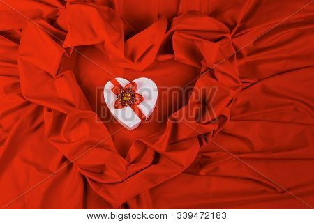 Valentines Greeting Card. White Cardboard Box In Shape Of Heart Wrapped In Ribbon Lay On A Red Cloth