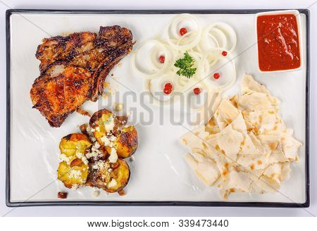 Grilled Beef Ribs And Baked Potato With Cheese. Onion Circles And Pita Bread, Red Sauce On A White B