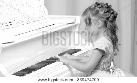 A Nice Little Girl Is Playing On A Big White Piano. The Concept Of Musical And Aesthetic Education O