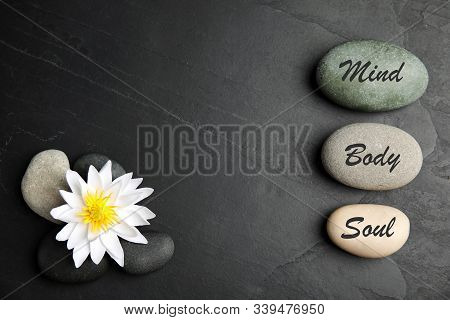 Lotus Flower, Stones With Words Mind, Body, Soul And Space For Text On Black Background, Flat Lay. Z