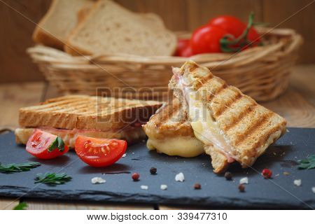 Club Or Toast Sandwiches On Black Tray. Grilled Sandwiches With Ham Salami, Tomato And Melted Cheese
