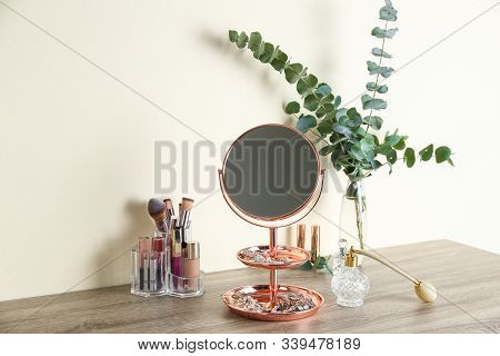 Mirror With Jewelry And Makeup Products On Wooden Table Near Light Wall