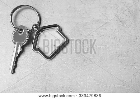 Key With Trinket In Shape Of House On Grey Stone Background, Top View And Space For Text. Real Estat