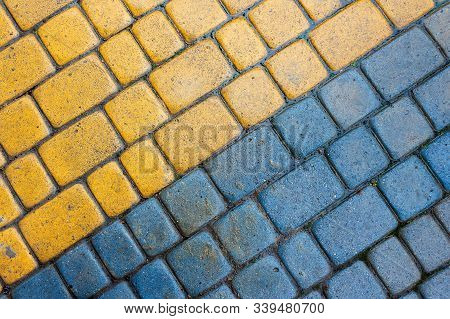 Yellow And Blue Cobbles Of Pavement Texture. Stone Masonry Floor Covering. Top View Of Wet Diagonal