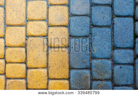 Yellow And Blue Cobbles Of Pavement Texture. Stone Masonry Floor Covering. Top View Of Vertical Wet