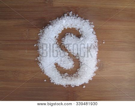 A Large Crystalline Salt Spreads On The Wooden Surface And Writes The Letter S.