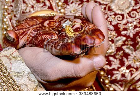 An Indian Bride And Groom Holding Their Hands With Ring During A Hindu Wedding Ritual