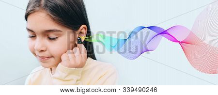 Cute Mixed Race Child Holding Hearing Aid Near Her Ear. Colored Sound Waves Showing Variety Of Sound