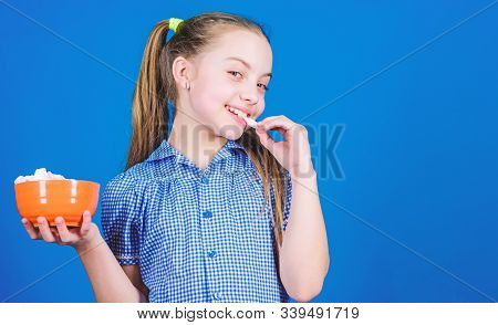 Girl Smiling Face Hold Bowl Sweet Marshmallows In Hand Blue Background. Kid Girl With Long Hair Like