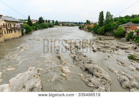 Panoramic Summer View Of The City Of Kutaisi, Georgia. Blue Sky With Clouds. River Rioni And Old Hou