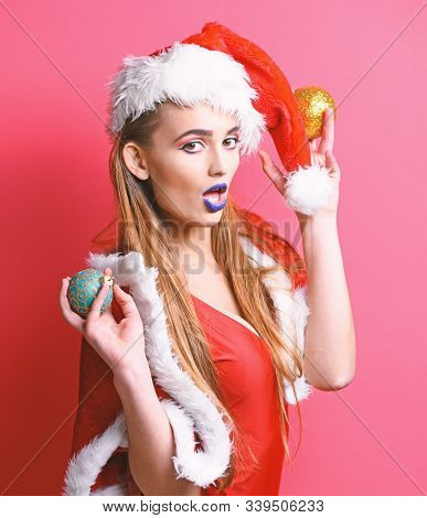 Girl Red Swimsuit And Santa Hat Hold Christmas Ball Decoration. Santa Girl Sexy With Make Up. Woman