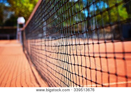 Tennis Net On The Tennis Court At The Day Time. Blurred