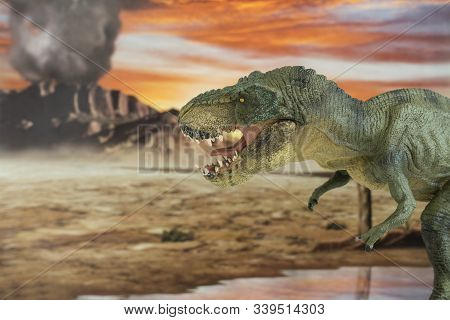 Portrait Of Walking And Dangerous Tyrannosaurus Rex With Erupting Volcano In The Background. Lateral