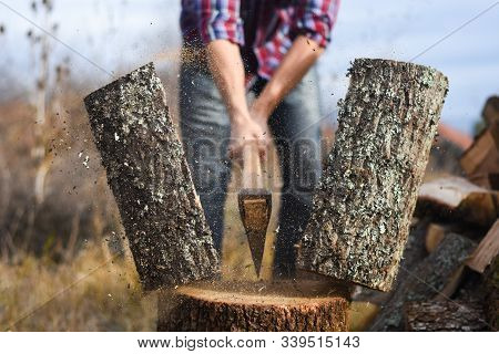 Lumberjack Chopping Wood For Winter, Young Man Chopping Woods With An Axe