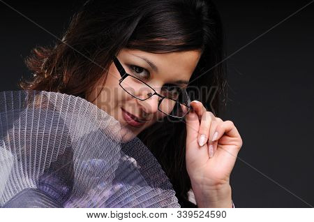 Portrait Of A Young And Mysterious Positive Woman Taking Off Glasses Posing On A Black Background. C