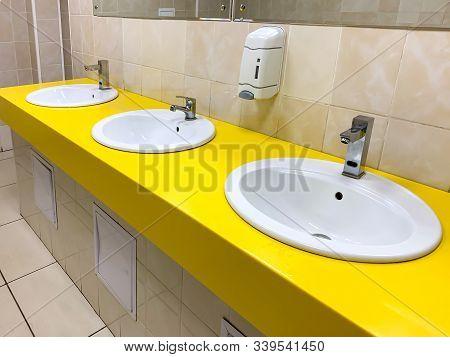 Row Of Yellow Modern Washing Basin In A Public Restroom.