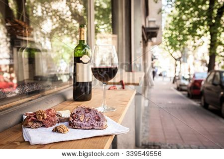 Glass And Bottle Of French Red Wine On Display On The Table Of A Terrace Of Paris With Slices Of Bag