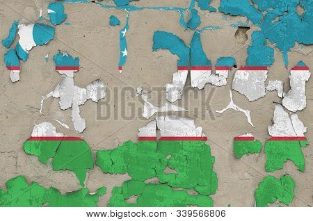 Uzbekistan flag depicted in paint colors on old obsolete messy concrete wall closeup. Textured banner on rough background poster