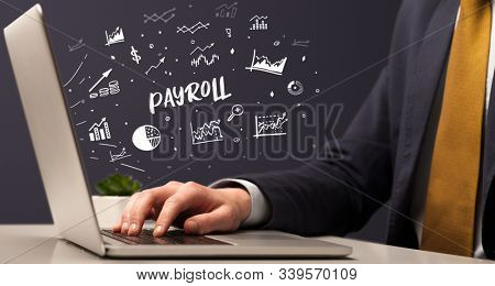 Businessman working on laptop with PAYROLL inscription, modern business concept