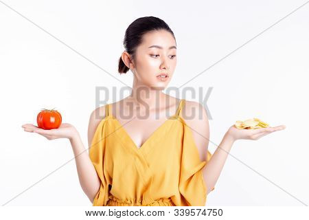 Diet Concept. Beautiful Young Asian Woman Looks At Delicious Snack, Potato Chip. Attractive Girl Con